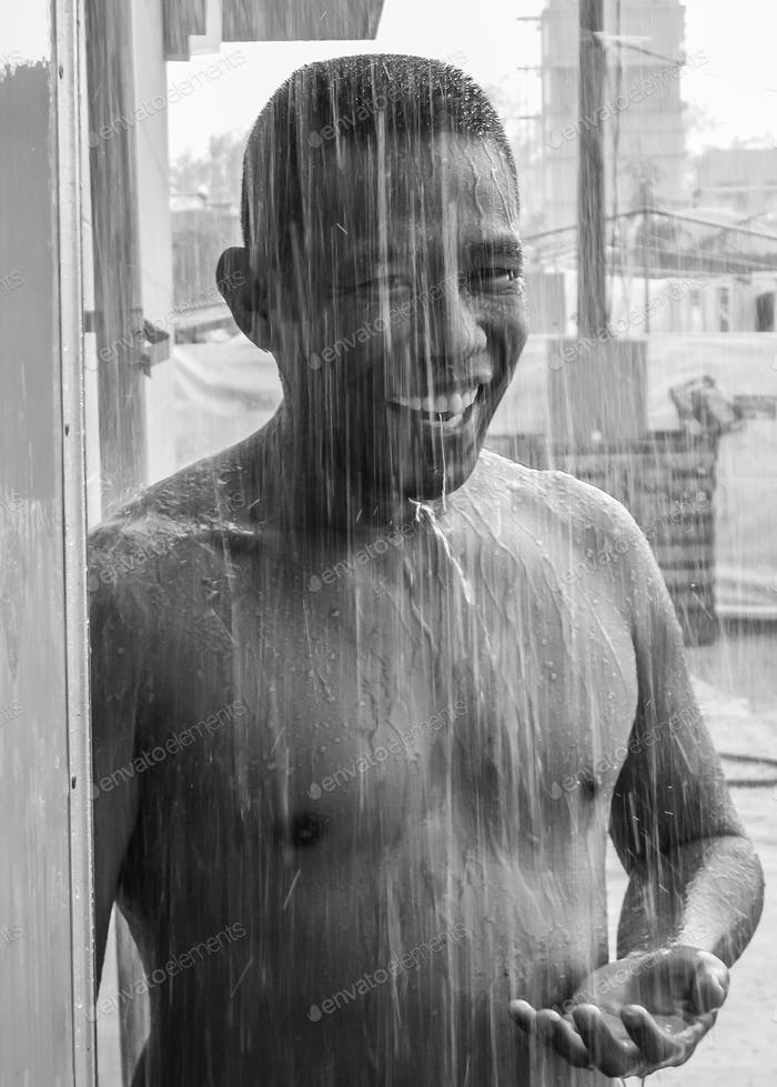 Black and white photo of an Asian man standing outside in a torrential downpour of rain to cool off.