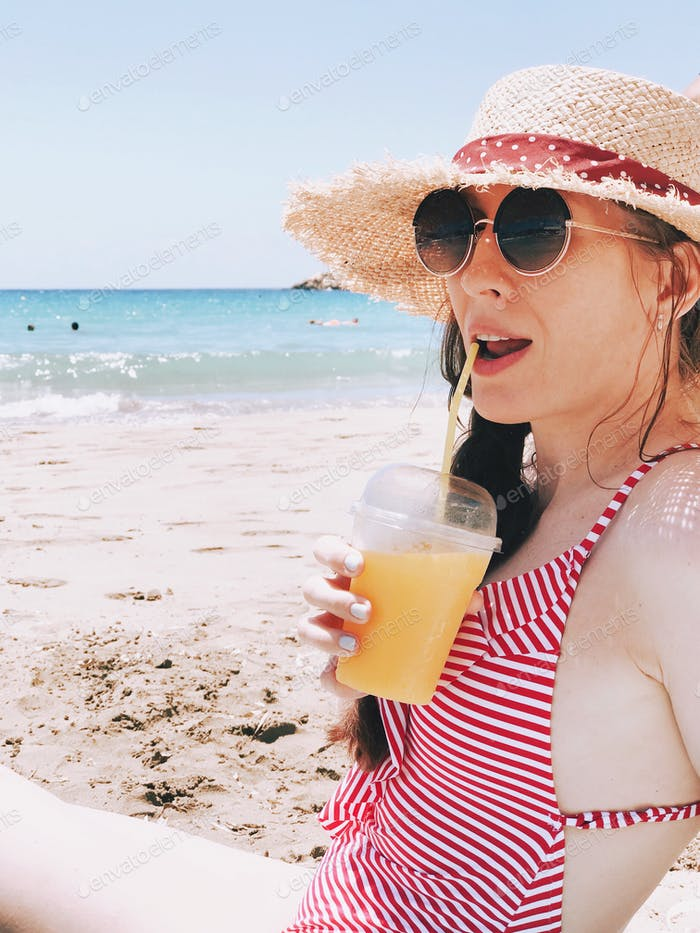 Girl in the straw hat drinking juice on the beach