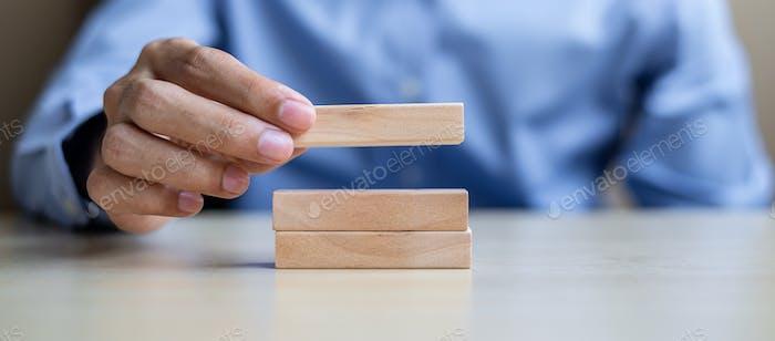 Hombre de negocios a mano sosteniendo bloques de construcción de madera sobre fondo de la mesa.