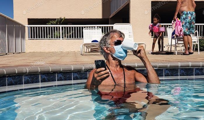 Genialer aktiver Babyboomer hat einen Schlitz in seine Gesichtsmaske geschnitten, um seinen Morgenkaffee in seine zu trinken