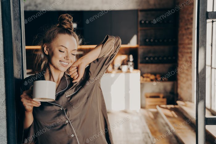 Happy beautiful brunette female stratching with cup of coffee in her hand while standing in kitchen