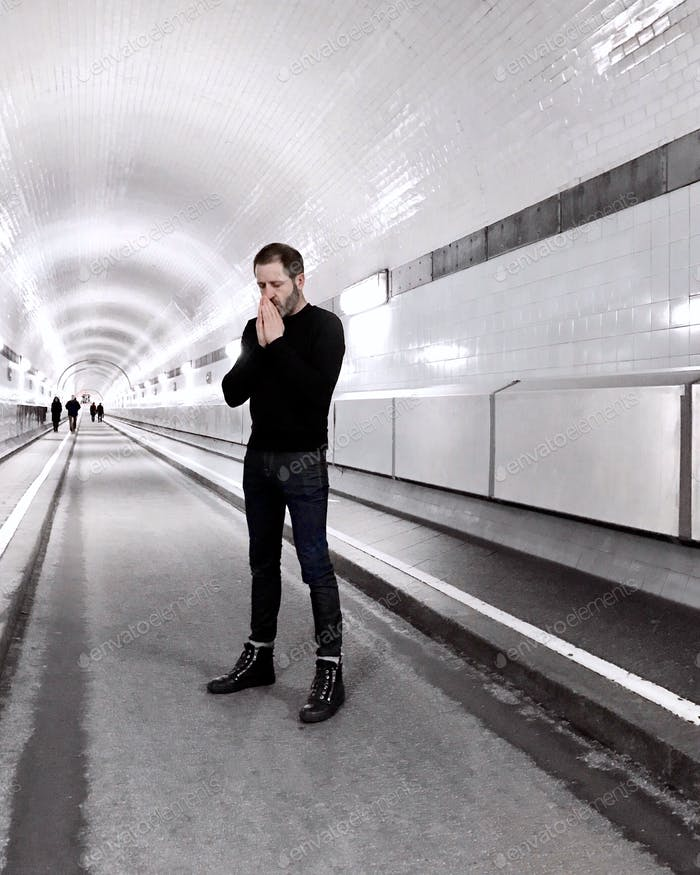 Vanishing point view of a man dressed in black in a white tunnel in a thinking or reflection pose.