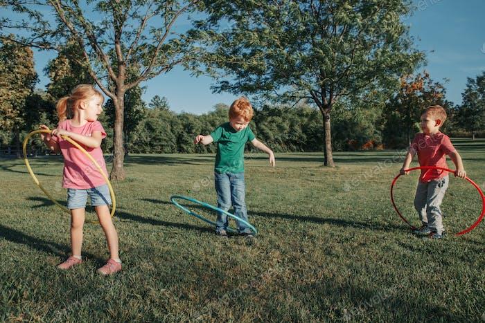 girl; boy; playing; hoola; hoop; park; sport; activity; recreation; fun; exercise; seasonal; hobby;