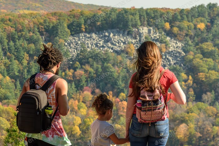 Young family standing at the top of the West Bluff at Devils Lake State Park overlooking the