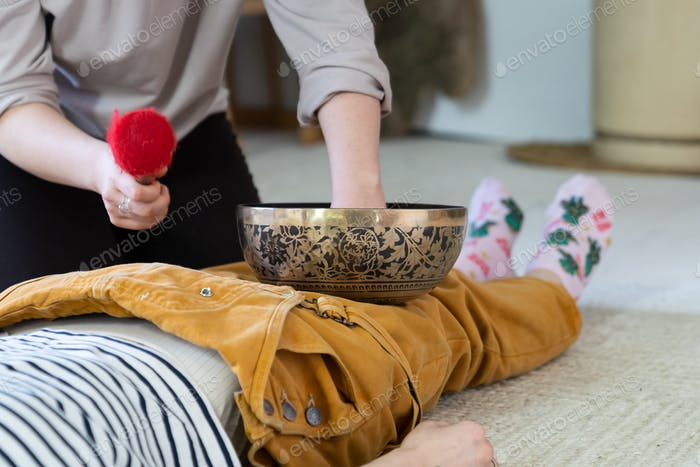 Tibetan singing bowls massage for recreation: woman use sound therapy for stress recovery at home