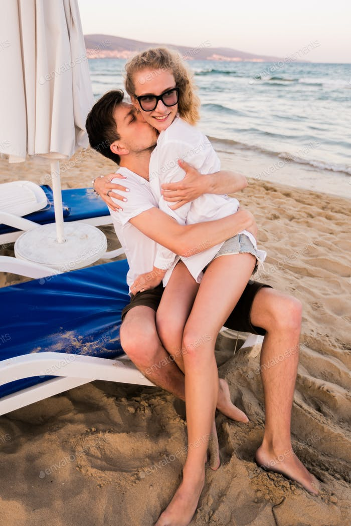 Lovely couple on the beach kissing and hugging