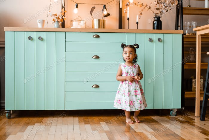 little African girl in a light floral dress in the kitchen at the blue chest of drawers
