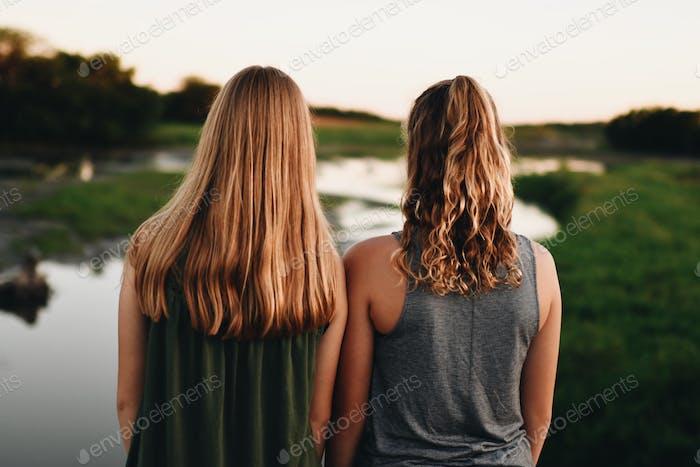 Девочки с светлыми волосами смотрят на озеро в сельской местности.