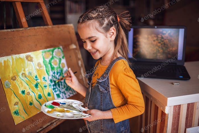 A cute girl with pallet, easel and brush drawing sunny flowers imaged in the screen of laptop artwor