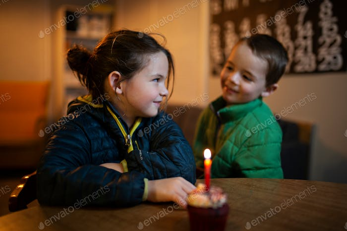 little girl and boy at a birthday party blowing out birthday candles
