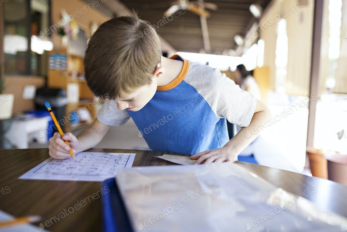 Boy working on schoolwork outside.