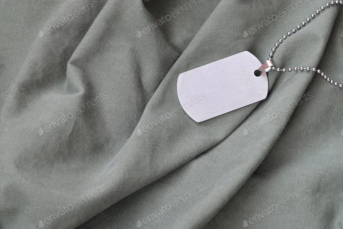 Silvery military beads with dog tag on dark green private fatigu