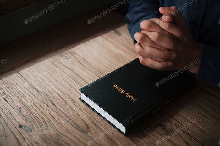 Man is reading and praying the scripture or holy bible on a wooden table with copy space. Religion,