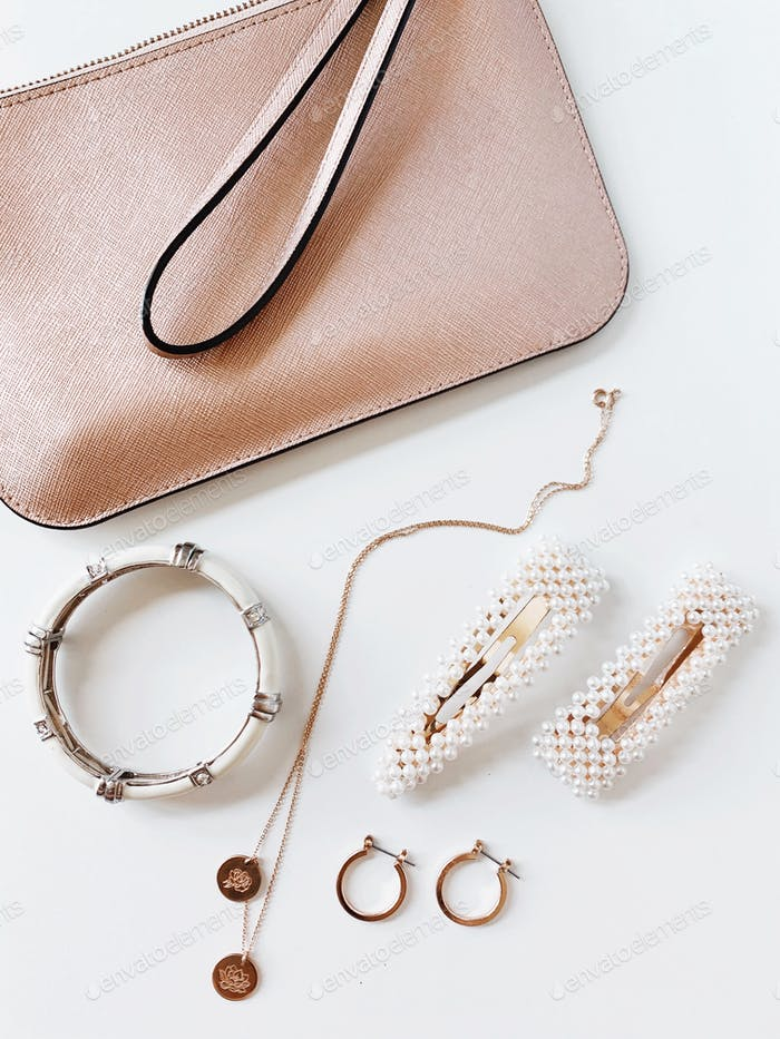A variety of different beauty items laying on a white background, spilling out of a pink clutch.