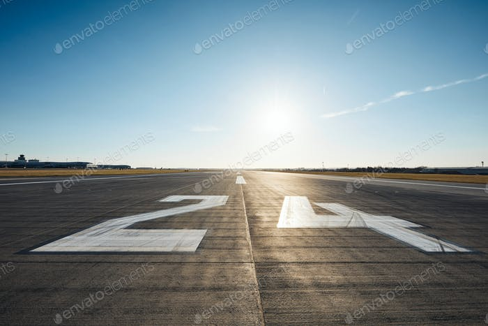 Surface level of airport runway with road marking and number 24 against clear sky