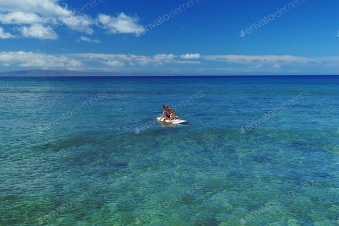 Mom and daughter on a surfboard
