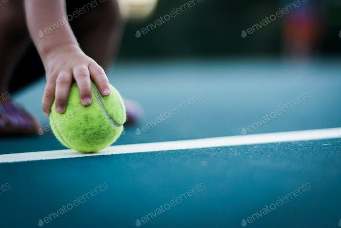 Die Hand des kleinen Mädchens greift auf einen Tennisball, der auf einem Tennisplatz platziert ist