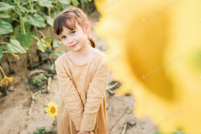 Happy child girl in the field of sunflowers