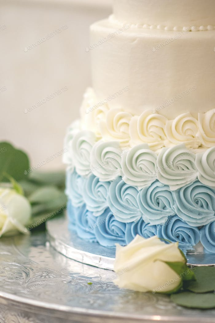 Blue ombré wedding cake with white roses and greenery