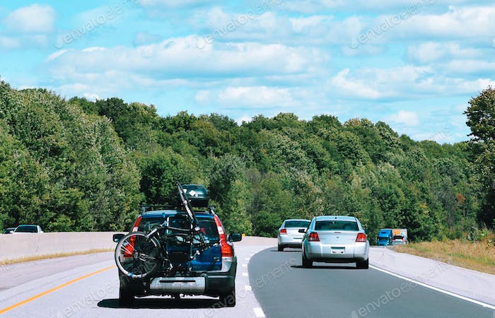 A car with a bike attached in the back driving on a highway
