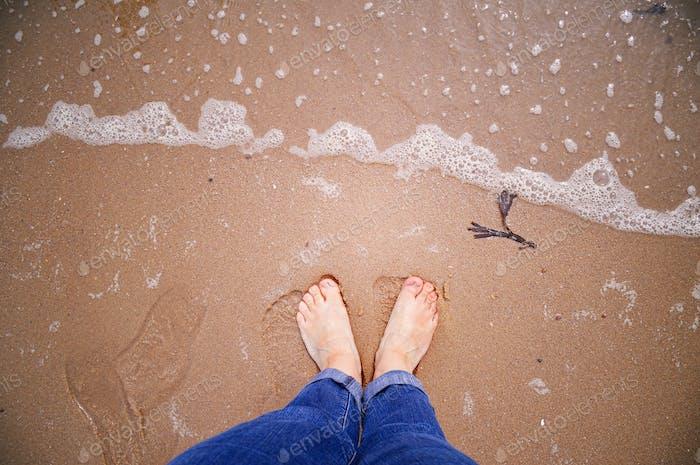 Bare feet in wet sand