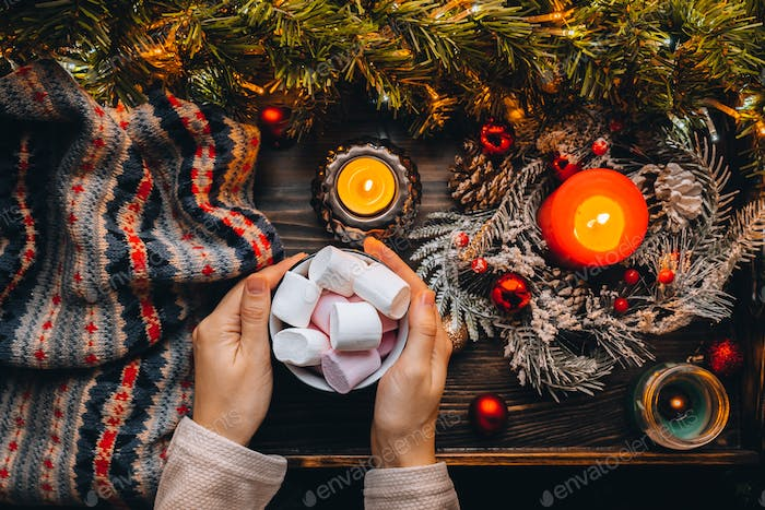 Cozy vibe. Hot chocolate with marshmallow in hands. Earl candle light, Christmas time, new year