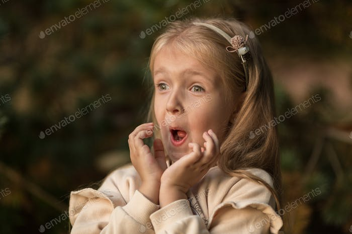 Portrait of adorable caucasian girl outdoor. Positive emotions on face