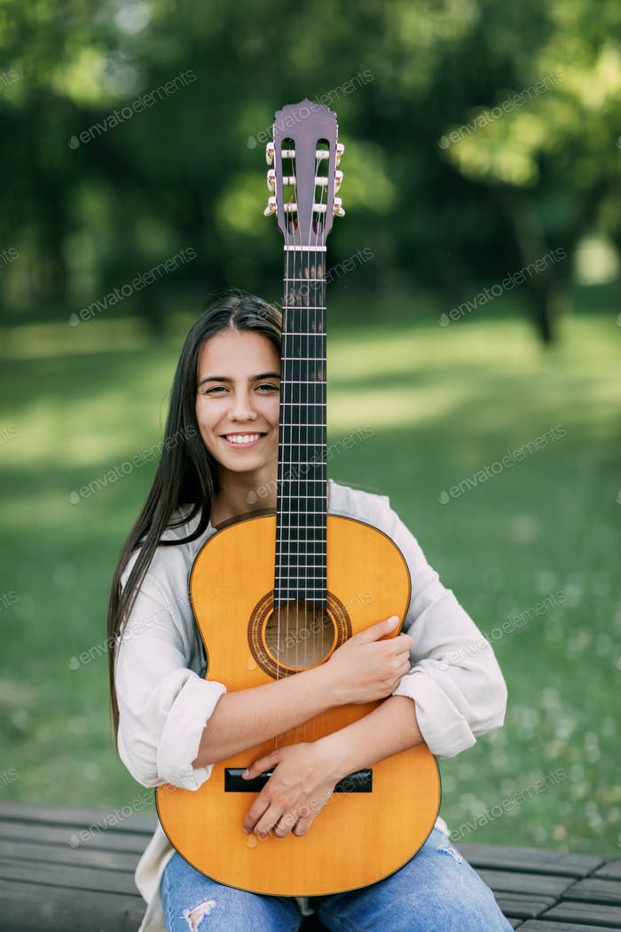 Portrait of a young girl guitarist who smiles and holds a guitar in her hands. Girl-musician, music,