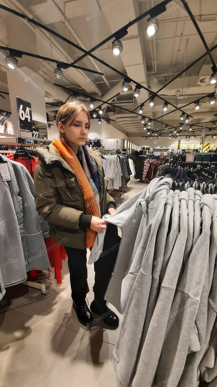 chica adolescente elige la ropa para sí misma en la tienda