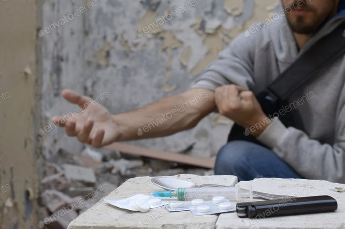Addict prepares veins on his hands for drug injection next to few pills from drug store