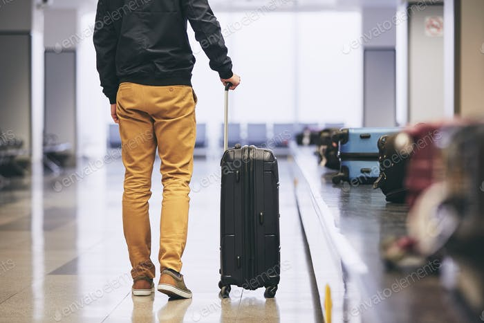 Man traveling by airplane. Young passenger holding his suitcase near baggage claim in airport termin