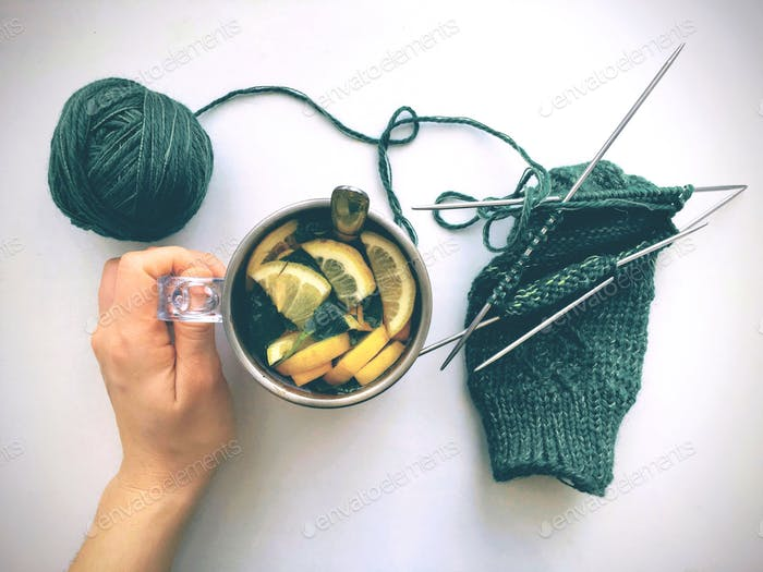 The hand holding the cup with tea with lemon and lemon balm, and in frame also knitting needles and