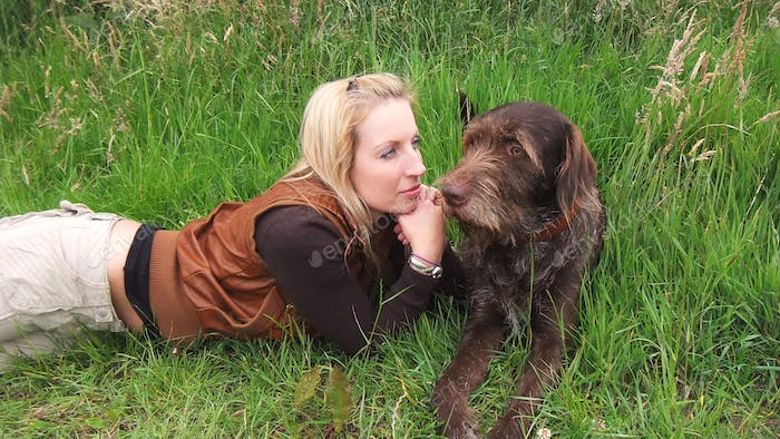 Blonde girl laying in the grass admiring her dog
