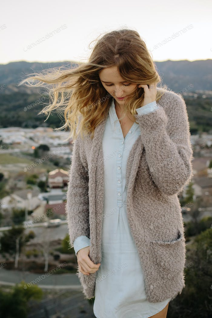 Young woman standing on a windy hilltop in a cozy sweater