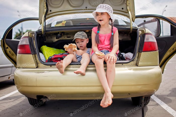 Kids having break during family road trip and eating bread in car on parking