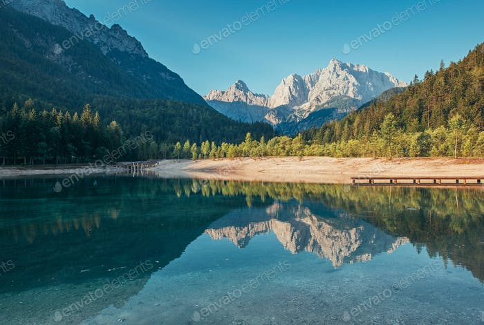 Morning reflections of the mountains, forest and hills in the Jasna Lake in Kranjska Gora, Slovenia.