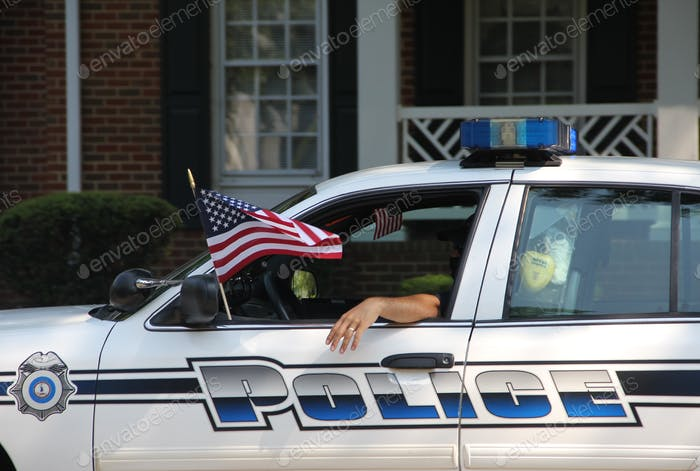 Police car with the United States flag during the July 4th parade.