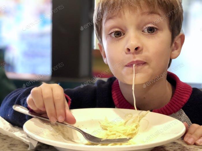 Boy slurping up spaghetti strand