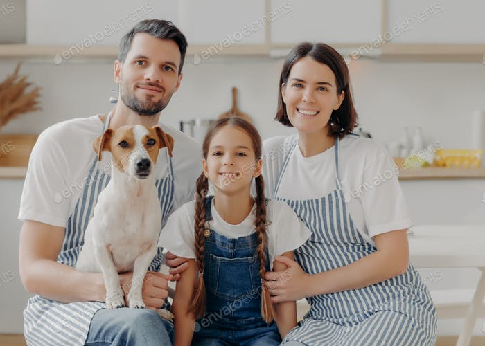 Family portrait of father, mother, daughter and pedigree dog pose together,  poses against kitchen
