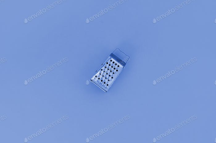 Stainless steel grater lies on a phantom classic blue paper