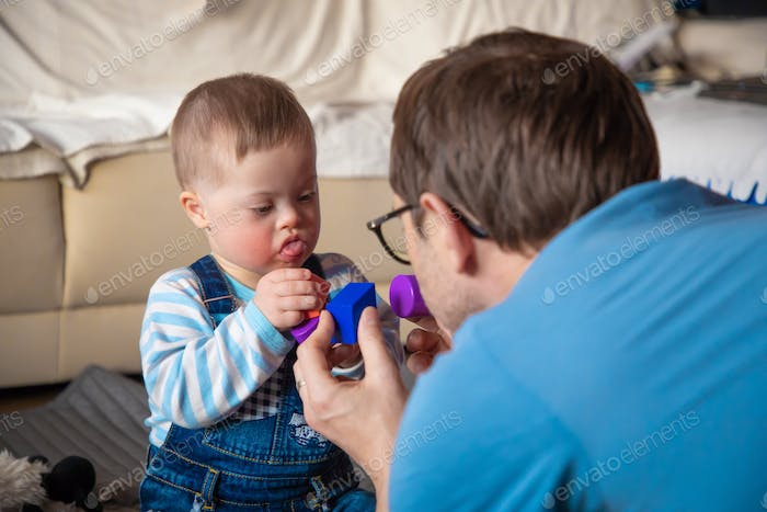 Cute baby boy with Down syndrome playing with daddy