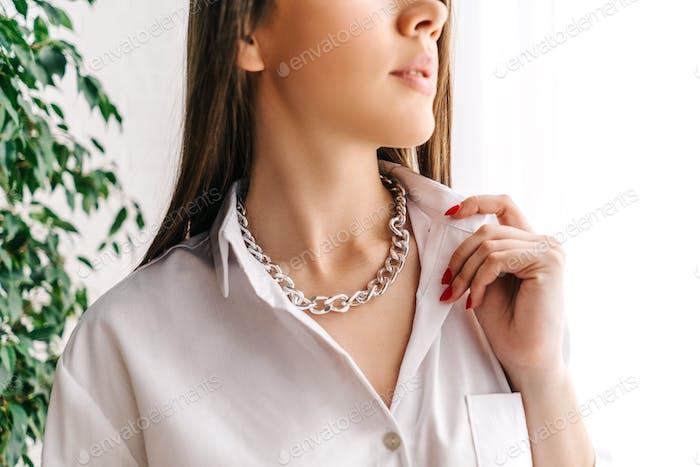 Silberne Bijouterie-Kette am Hals der Frau. Weißer Hintergrund mit grüner Pflanze.