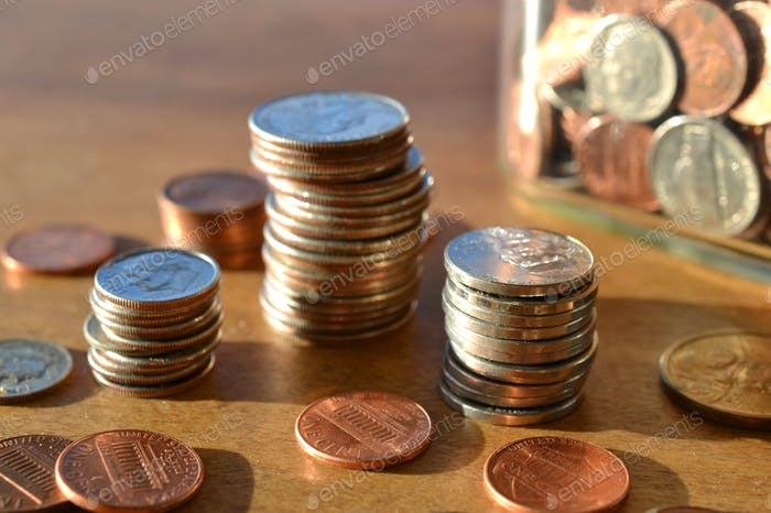 Stacks piles of spare change coins, pennies, dimes, nickels, quarters, loose change jar, saving