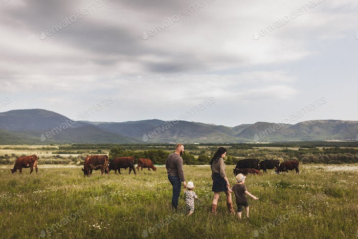 Family walking outdoors on countryside. Mountain view, farm with cows