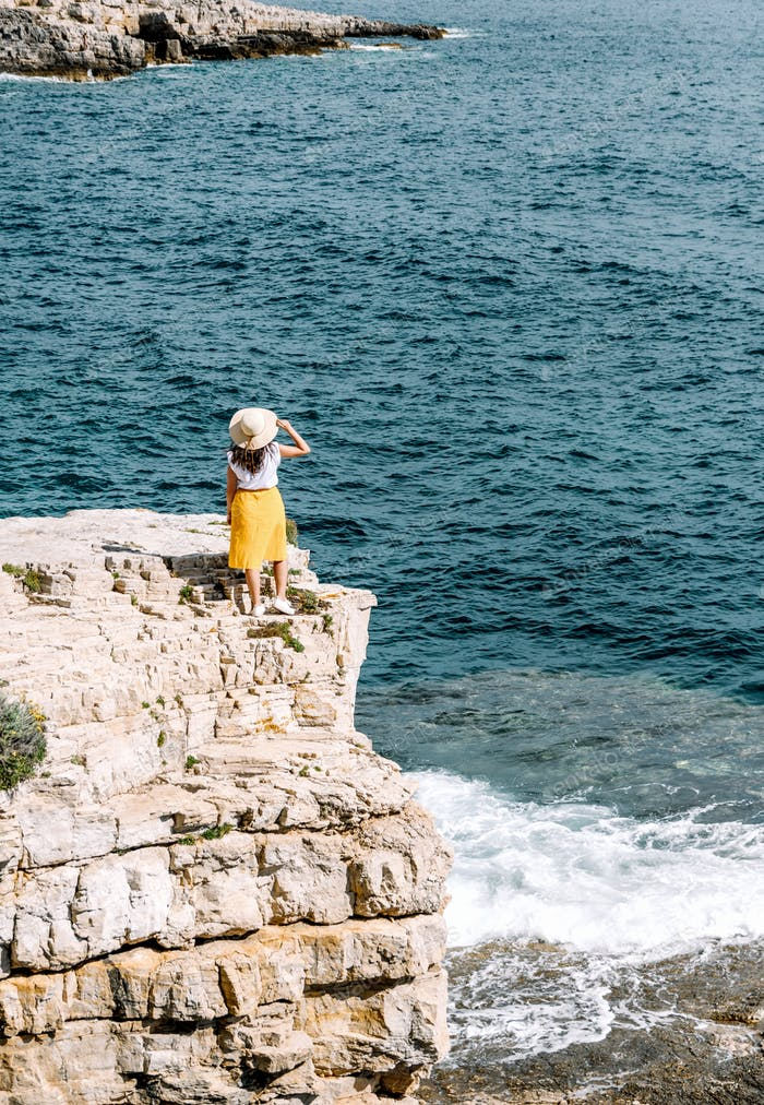 Woman in summer outfit, white top and yellow skirt, standing on cliffs above sea