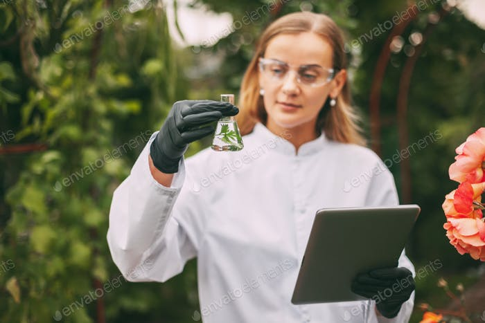 A botanist woman holding a tablet and a magnifying glass examines a plant sample during