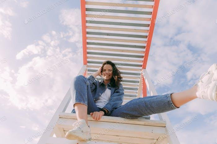 a young happy girl in jeans is sitting on a crossbar and laughing against the sky