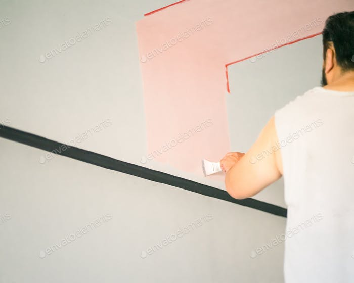 man painting wall line with pastel pink, view from behind