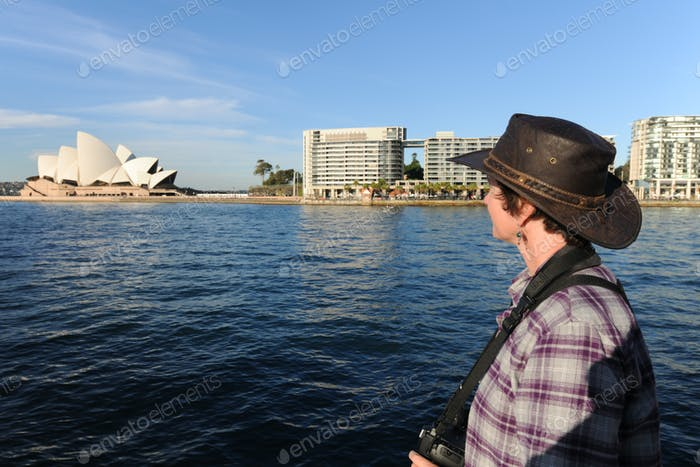 Woman with camera looking across the harbour towards Sydney Opera House, Sydney, Australia