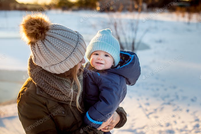Mom and baby outside in the snow - all dressed up in winter gear